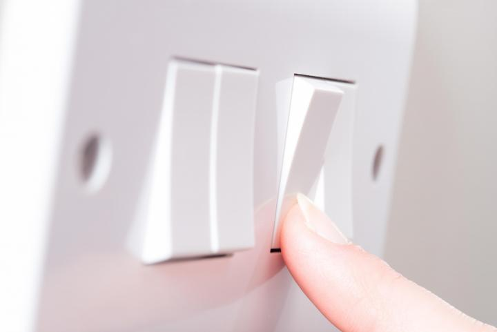 Image of a finger pressing a light switch on a wall.