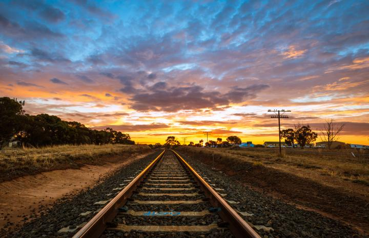 An image of railway tracks in a country landscape running towards a horizon with the sun setting in the background.