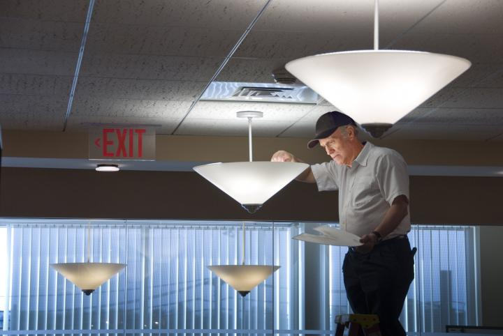 Electrician changing a light bulb