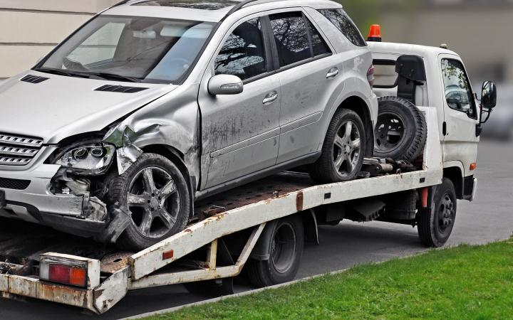 An image showing a silver SUV with a crushed front corner on the back of a tow truck.