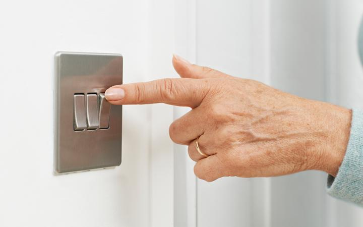 Woman's hand switching a light switch