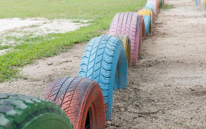 An image showing a series of tyres spray-painted in different colours and half-buried in sand to form a low barrier near some grass.