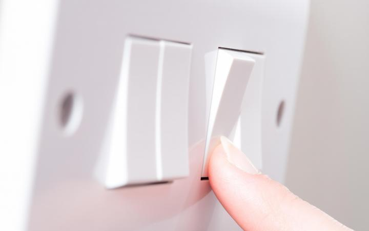 Image of a finger pressing a light switch on a wall