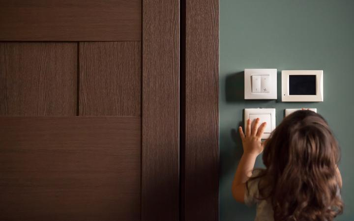 A photo showing a young girl pressing a light switch on a wall.