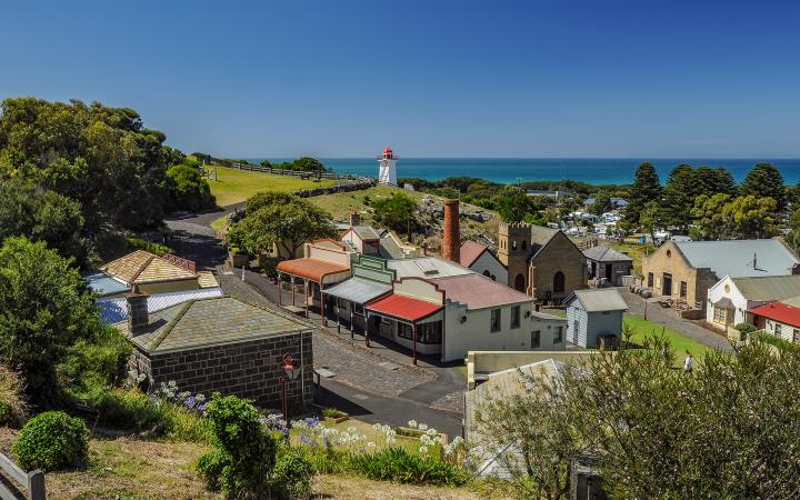 A photo of Warrnambool township with the sea and a lighthouse in the background.