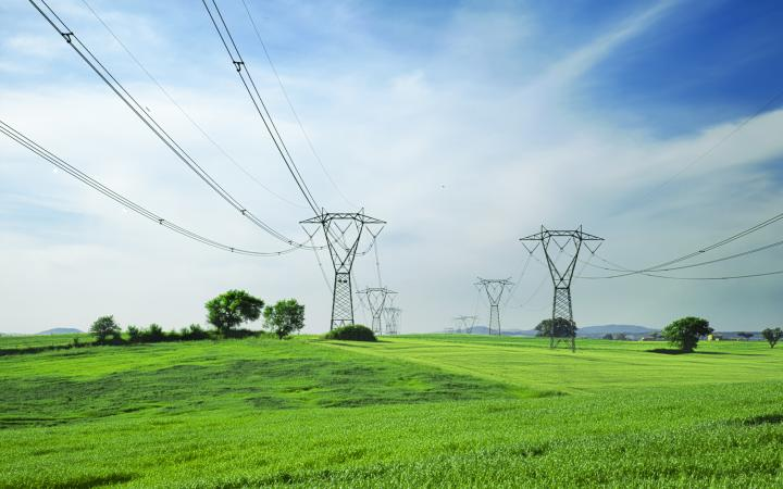 An image showing large powerlines running across several large green paddocks.