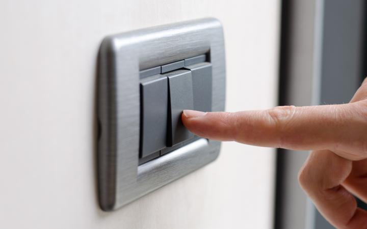 An image showing a hand pressing a grey electric switch on a wall.