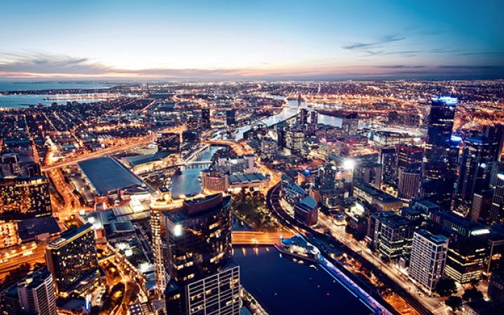 Birds-eye view of Melbourne CBD at sunset with city lights on