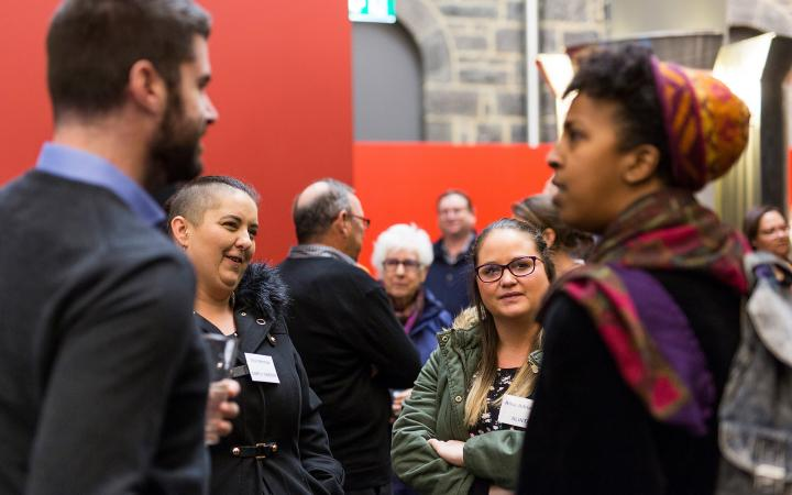 An image of two women (in focus) and a man and woman (foreground, blurred) chatting to each other at the commission's family violence forum on 30 August 2018.