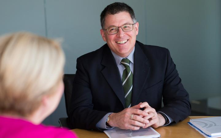 An image showing Dr Ron Ben-David, Chairperson of the Essential Services Commission, seated at a table and talking to someone with their back to the camera.